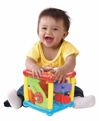 This is an image of a  baby playing with a busy learners activity cube.
