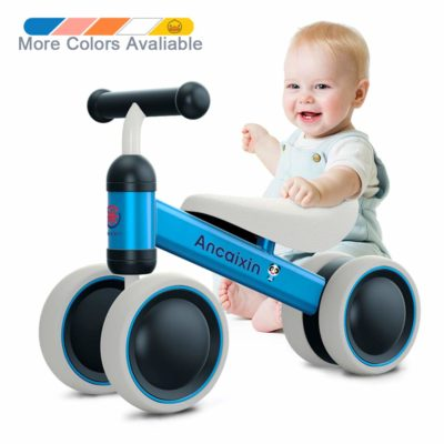 This is an image of a baby who is about to ride a blue balance bike.