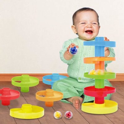 This is an image of a baby playing with a colorful spinning swirl ball ramp toy.
