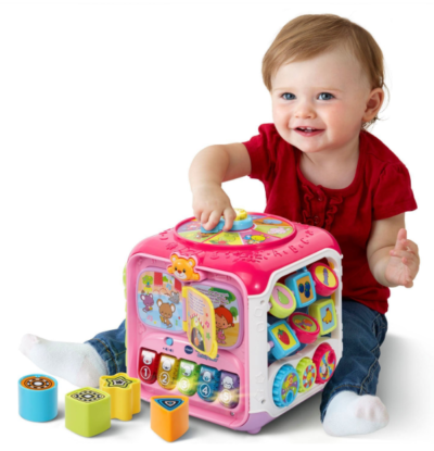 This is an image of a baby playing with a pink activity cube.