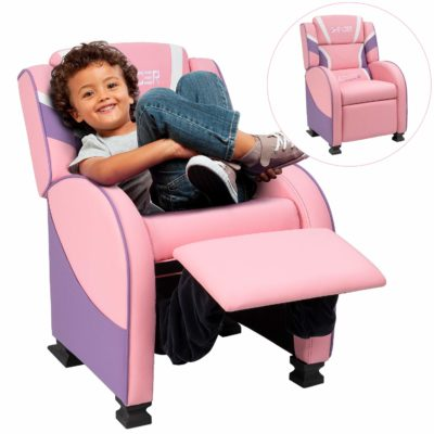 This is an image of a little boy sitting on a pink children's recliner.
