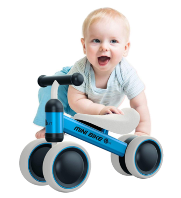 This is an image of a baby who is about to ride on a blue bike.