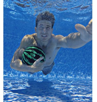 This is an image of a man holding a watermelon ball while swimming.