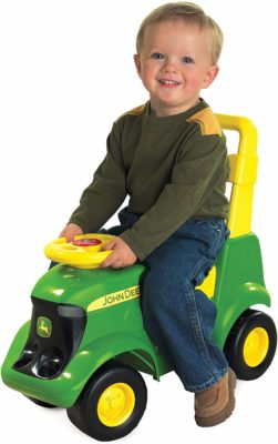 This is an image of a little boy riding the green and yellow ride on toy by John Deere.