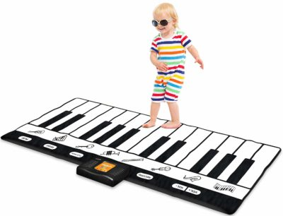 This is an image of a little kid playing with a keyboard playmat by Play22.