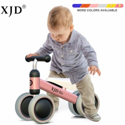 This is an image of a toddler riding a pink balance bike by XJD.