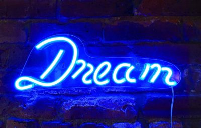 This is an image of a neon blue 'Dream' LED sign by Isaac Jacobs.