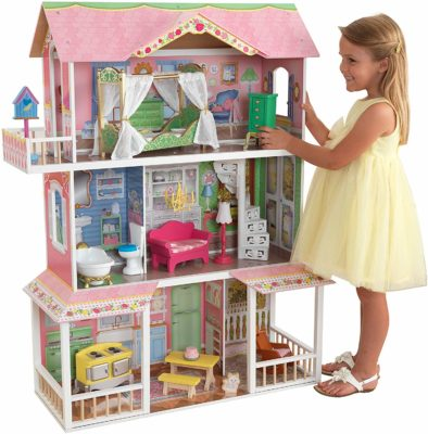 This is an image of a little girl playing with the Savannah dollhouse by KidKraft.