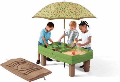 This is an image of kids playing using the sand and water activity table with umbrella by Step2.