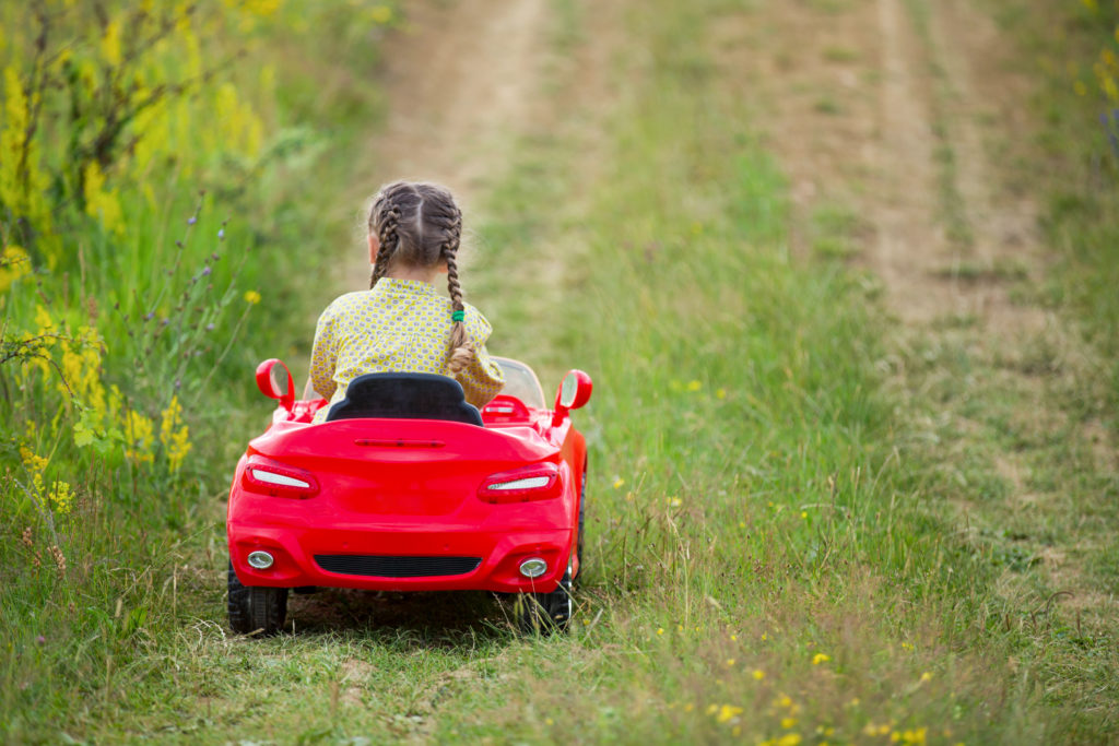this is an image of a girl riding a toy red car