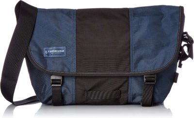 This is an image of a dusk black and blue messenger bag for men by Timbuk2.
