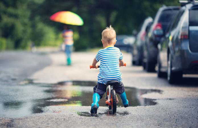 this is an image of a boy on a balance bike riding it through puddles