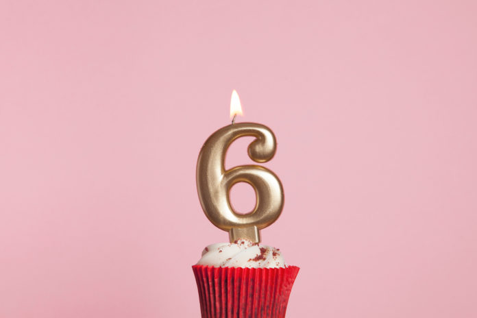 this is an image of a cupcake with a 6th birthday candle on it