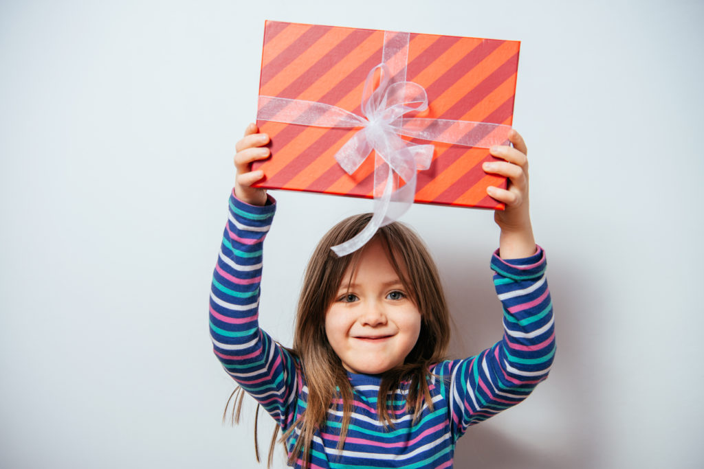 young girl holding up a present and smiling