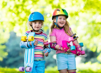 this is an image of Children riding skateboard in summer park