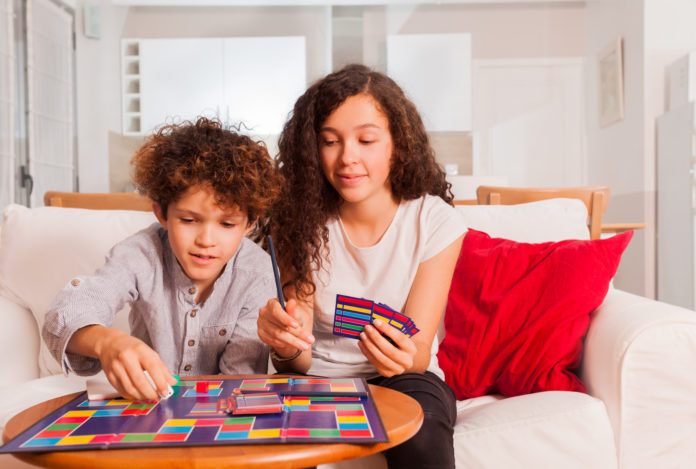 this is an image of a tween boy and girl playing a board game