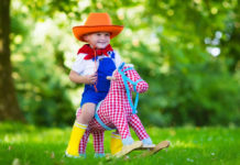 Little boy dressed up as cowboy playing with his toy rocking horse in a summer park. Kids play outdoors. Children in Halloween costumes at trick or treat. Toys for preschooler or toddler child.