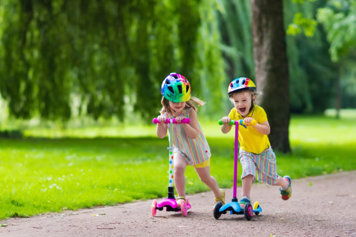 this is an image of two kids on scooters in the park