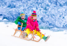 this is an image of two kids riding a sled in the snow