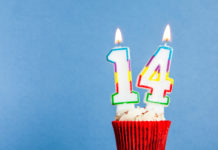 this is an image of a Number 14 birthday candle in a cupcake against a blue background