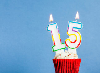 this is an image of a Number 15 birthday candle in a cupcake against a blue background