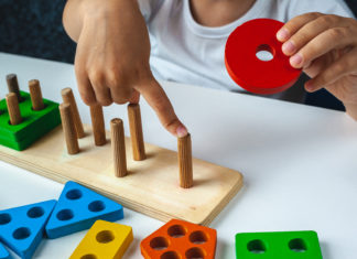 this is an image of a A child playing with a Wooden educational toys