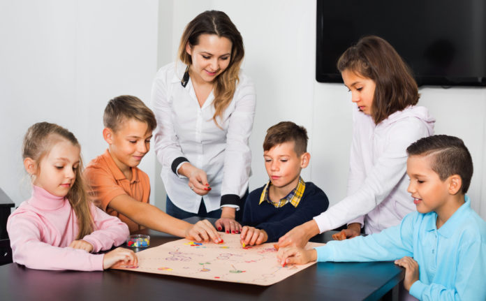 this is an image of 8 year olds playing a board game