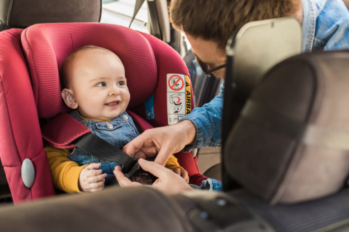 this is an image of a Father fastening his little baby in the car seat
