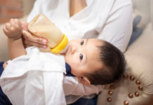 this is an image of Newborn baby is drinking milk from bottle by mom