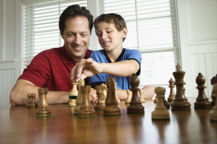 this is an image of a 10 year old playing a board game with his dad