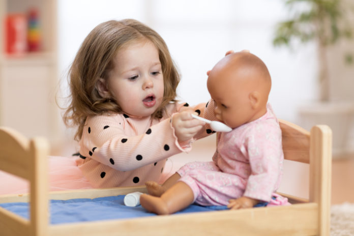 this is an image of a toddler girl playing with a baby doll in a crib