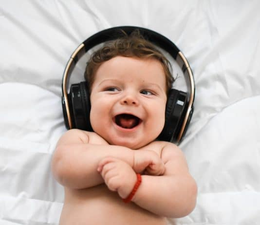 baby smiling and wearing headphones