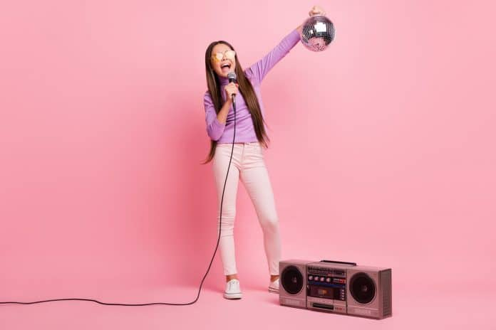 girl singing to her radio speakers